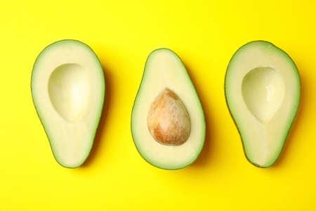 Cut fresh ripe avocados on yellow background, flat lay