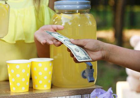 Little girl selling natural lemonade to African-American boy in park, closeup. Summer refreshing drink Stockfoto