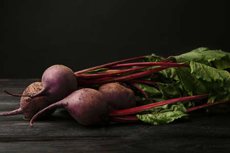 Fresh beets with leaves on dark wooden table against black background. Space for text Banco de Imagens