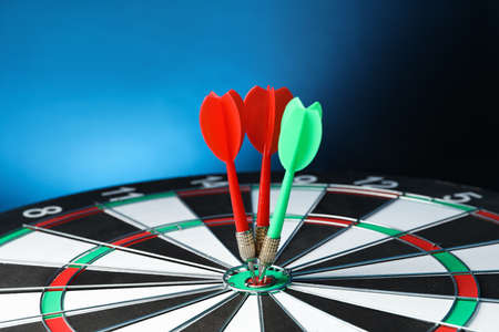 Arrows hitting target on dart board against blue background Archivio Fotografico