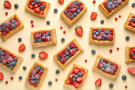 Fresh delicious puff pastry with sweet berries on beige background, flat lay