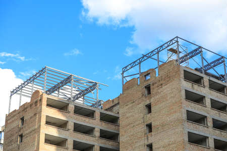 Unfinished building against blue sky. Construction safety rules