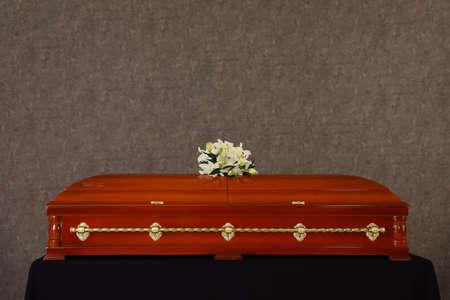 Begräbnisschatulle aus Holz mit weißen Lilien an grauer Wand