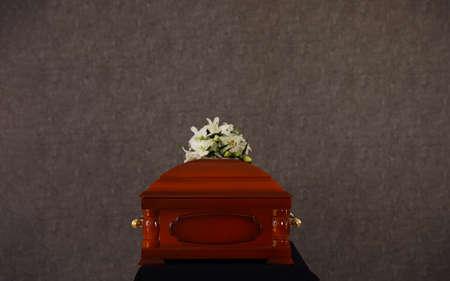 Begräbnisschatulle aus Holz mit weißen Lilien an grauer Wand Standard-Bild
