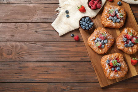 Fresh delicious puff pastry with sweet berries on wooden background, flat lay. Space for text Reklamní fotografie