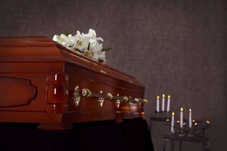 Drewniana trumna z białymi liliami w domu pogrzebowym