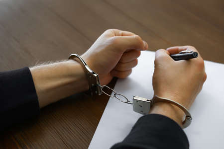 Criminal in handcuffs writing confession at desk, closeup