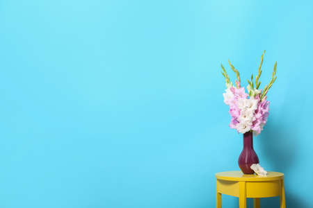 Vase with beautiful gladiolus flowers on wooden table against blue background. Space for text Stock fotó