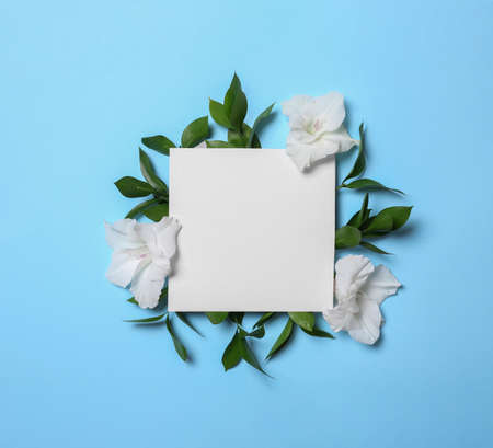 Beautiful gladiolus flowers and blank card on blue background, flat lay. Space for text Stock fotó