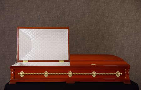 Offener hölzerner Bestattungssarg auf Ständer an der grauen Wand