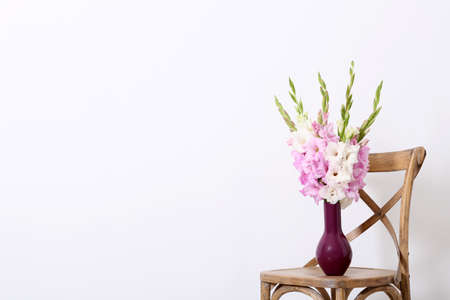 Vase with beautiful gladiolus flowers on wooden chair against white background