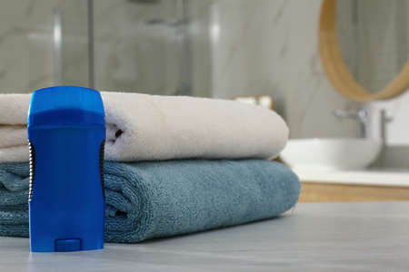 Deodorant with clean towels on table in bathroom. Space for text