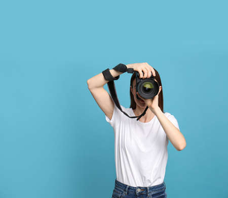 Professional photographer taking picture on light blue background