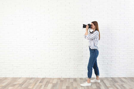 Professional photographer taking picture near white brick wall. Space for text