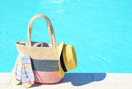 Bag with beach accessories near swimming pool on sunny day. Space for text