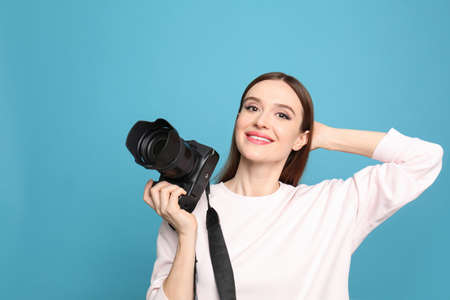Professional photographer with modern camera on light blue background
