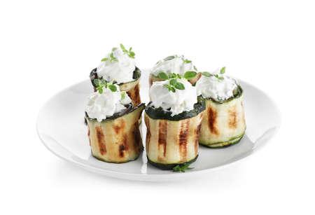 Tasty stuffed zucchini rolls on white background