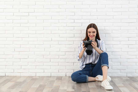 Professional photographer with modern camera near white brick wall. Space for text 写真素材