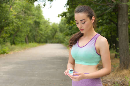 Young woman checking pulse with medical device after training in park. Space for text