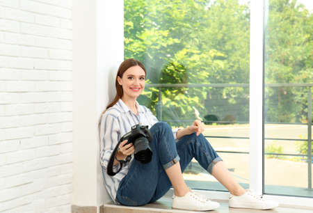 Professional photographer with modern camera sitting near window indoors