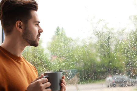 Thoughtful handsome man with cup of coffee near window indoors on rainy day 版權商用圖片