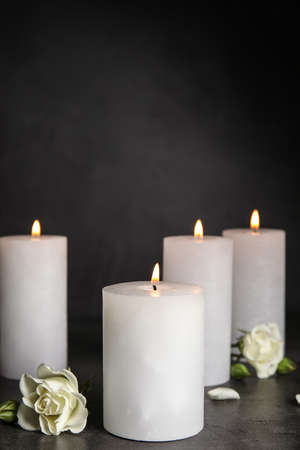 Burning candles and beautiful flowers on grey table, space for text