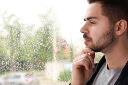 Bel homme réfléchi près de la fenêtre à l'intérieur le jour de pluie