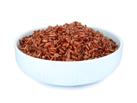 Bowl with delicious cooked brown rice on white background