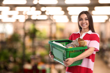 Young woman with shopping basket full of different products in supermarket, space for text
