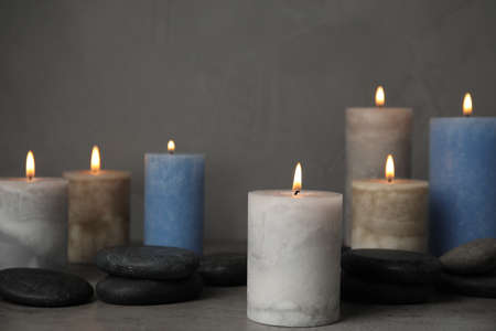 Burning candles and spa stones on grey table 版權商用圖片