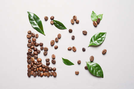 Fresh green coffee leaves and beans on light background, flat lay