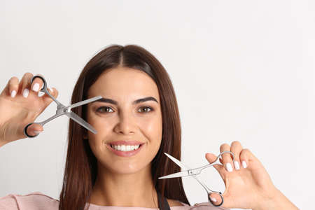 Young hairstylist holding professional scissors on light background Banco de Imagens