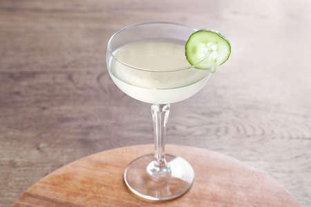 Glass of tasty cucumber martini on wooden table