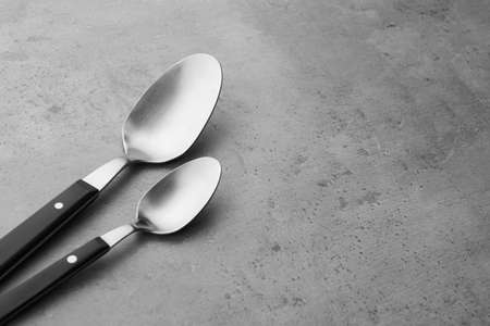 Clean empty table spoons on grey background, space for text