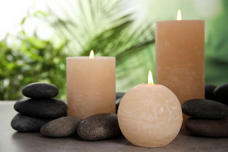 Burning candles and spa stones on table against blurred green background 版權商用圖片
