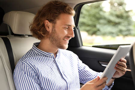 Attractive young man with tablet on backseat in luxury car