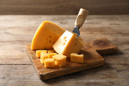 Serving board with delicious cheese on wooden table Фото со стока