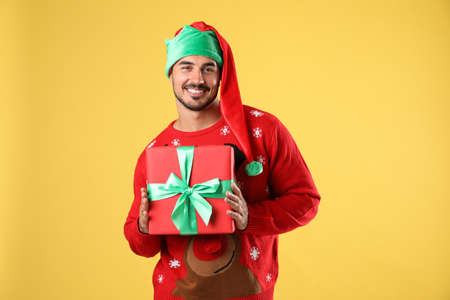 Happy man in Christmas sweater and elf hat holding gift box on yellow background