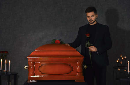 Sad young man near funeral casket with red rose in chapel