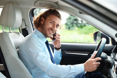 Attractive young man talking on phone while driving car Stockfoto - 128608901