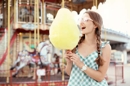 Young woman with cotton candy in amusement park. Space for text Imagens - 128608916