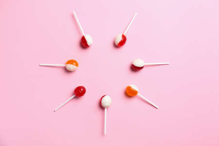 Flat lay composition with delicious lollipop candies on pink background. Space for text