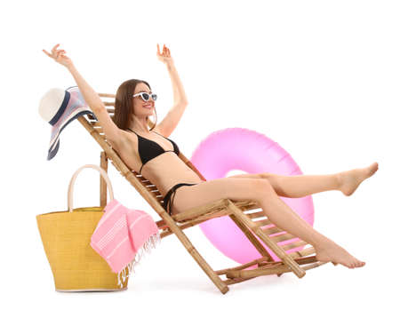 Young woman with beach accessories on sun lounger against white background Reklamní fotografie