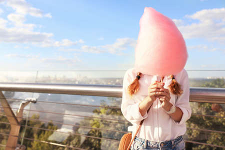 Young woman with cotton candy outdoors on sunny day. Space for text