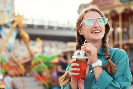 Young woman with refreshing drink in amusement park. Space for text