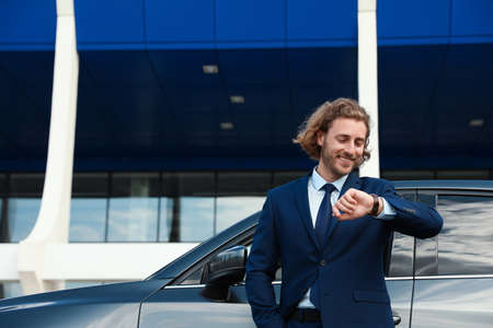 Attractive young man checking time near luxury car outdoors Stockfoto