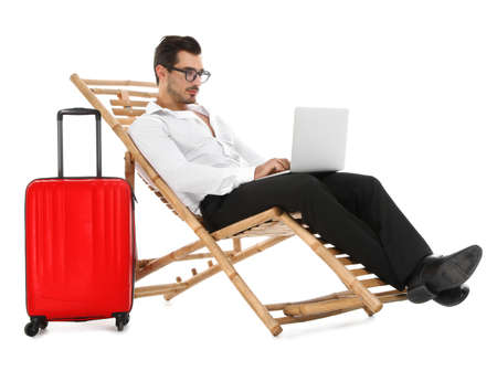 Young businessman with laptop and suitcase on sun lounger against white background. Beach accessories 版權商用圖片 - 128609317