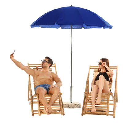 Young couple taking selfie on sun loungers under umbrella against white background. Beach accessories