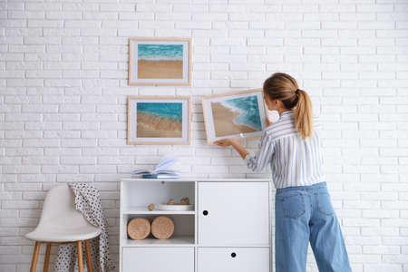 Decorator hanging picture on white brick wall in room. Interior design Archivio Fotografico