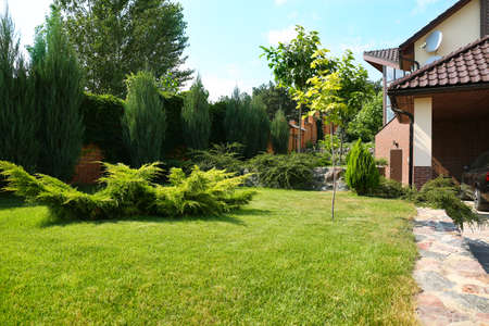 Landscape with modern house and beautiful garden on sunny day Stockfoto